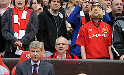 A serious looking Arsene Wenger  sits on the bench as a Man Utd fan wearing a Eric Cantona mask  enjoys the match behind him.  Manchester United v Arsenal at Old Trafford, 16th May 2009.