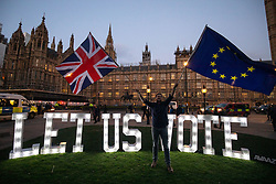 """March 27, 2019 - London, London, UK - London, UK. Campaigning group Avaaz install 1.2 metre-tall illuminated letters spelling out """"LET US VOTE"""" outside the Houses of Parliament. This evening MPs are expected to vote on a series of indicative votes on alternative proposals to British Prime Minister Theresa May's withdrawal agreement. (Credit Image: © Tom Nicholson/London News Pictures via ZUMA Wire)"""