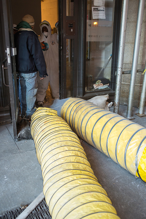 Workers wearing protective clothing installing ventilation ducts in the Albany Street service entrance to 90 West Street.