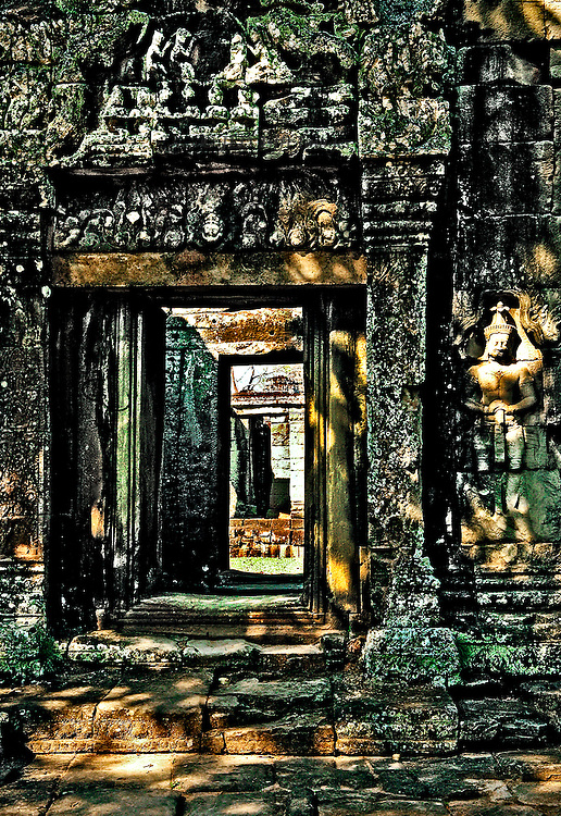 Angkor: doorways at Banteay Kdei recede in perspective.  Saturated colors of green moss, yellow sunlight, blue and aqua rock.  Not a realistic view.