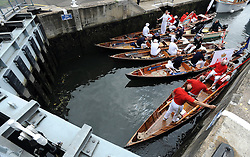 © licensed to London News Pictures. LONDON, UK.  18/07/11. The uppers group together in a lock. Swan Upping takes place on the River Thames today (18 July 2011). Swan Upping dates from medieval times, when The Crown claimed ownership of all mute swans which were considered an important food source for banquets and feasts. Today, the cygnets are weighed and measured to obtain estimates of growth rates and the birds are examined for any sign of injury, commonly caused by fishing hook and line. The cygnets are ringed with individual identification numbers by The Queen's Swan Warden, whose role is scientific and non-ceremonial. The Queen's Swan Marker produces an annual report after Swan Upping detailing the number of swans, broods and cygnets counted during the week. Mandatory Credit Stephen Simpson/LNP