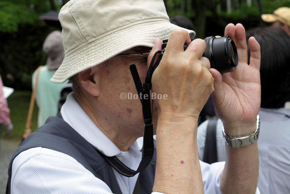 senior Asian man taking pictures
