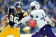 Iowa Hawkeyes running back Akrum Wadley (25) tries to hold off Northwestern Wildcats safety Godwin Igwebuike (16) during the third quarter of their game at Kinnick Stadium in Iowa City on Saturday, November 1, 2014.