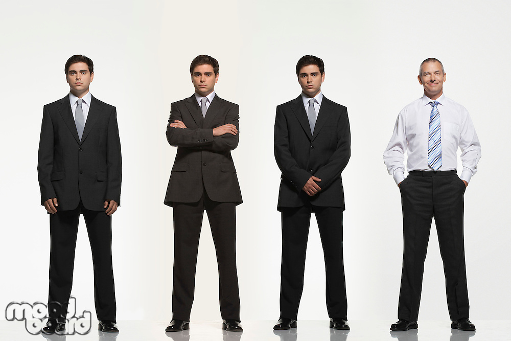 Businessmen standing side by side arms crossed by side clasped in pockets digitally enhanced
