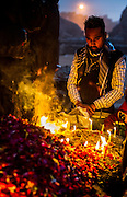 "8th January 2015, New Delhi, India. A man stands in quiet prayer by burning candles, incense sticks and flower petals left by believers hoping to get wishes granted by Djinns in the ruins of Feroz Shah Kotla in New Delhi, India on the 8th January 2015<br /> <br /> PHOTOGRAPH BY AND COPYRIGHT OF SIMON DE TREY-WHITE a photographer in delhi<br /> + 91 98103 99809. Email: simon@simondetreywhite.com<br /> <br /> People have been coming to Firoz Shah Kotla to leave written notes and offerings for Djinns in the hopes of getting wishes granted since the late 1970's. Jinn, jann or djinn are supernatural creatures in Islamic mythology as well as pre-Islamic Arabian mythology. They are mentioned frequently in the Quran  and other Islamic texts and inhabit an unseen world called Djinnestan. In Islamic theology jinn are said to be creatures with free will, made from smokeless fire by Allah as humans were made of clay, among other things. According to the Quran, jinn have free will, and Iblīs abused this freedom in front of Allah by refusing to bow to Adam when Allah ordered angels and jinn to do so. For disobeying Allah, Iblīs was expelled from Paradise and called ""Shayṭān"" (Satan).They are usually invisible to humans, but humans do appear clearly to jinn, as they can possess them. Like humans, jinn will also be judged on the Day of Judgment and will be sent to Paradise or Hell according to their deeds. Feroz Shah Tughlaq (r. 1351–88), the Sultan of Delhi, established the fortified city of Ferozabad in 1354, as the new capital of the Delhi Sultanate, and included in it the site of the present Feroz Shah Kotla. Kotla literally means fortress or citadel."