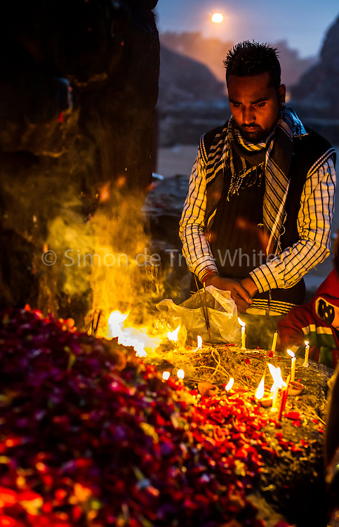 8th January 2015, New Delhi, India. A man stands in quiet prayer by burning candles, incense sticks and flower petals left by believers hoping to get wishes granted by Djinns in the ruins of Feroz Shah Kotla in New Delhi, India on the 8th January 2015<br /> <br /> PHOTOGRAPH BY AND COPYRIGHT OF SIMON DE TREY-WHITE a photographer in delhi<br /> + 91 98103 99809. Email: simon@simondetreywhite.com<br /> <br /> People have been coming to Firoz Shah Kotla to leave written notes and offerings for Djinns in the hopes of getting wishes granted since the late 1970's. Jinn, jann or djinn are supernatural creatures in Islamic mythology as well as pre-Islamic Arabian mythology. They are mentioned frequently in the Quran  and other Islamic texts and inhabit an unseen world called Djinnestan. In Islamic theology jinn are said to be creatures with free will, made from smokeless fire by Allah as humans were made of clay, among other things. According to the Quran, jinn have free will, and Iblīs abused this freedom in front of Allah by refusing to bow to Adam when Allah ordered angels and jinn to do so. For disobeying Allah, Iblīs was expelled from Paradise and called &quot;Shayṭān&quot; (Satan).They are usually invisible to humans, but humans do appear clearly to jinn, as they can possess them. Like humans, jinn will also be judged on the Day of Judgment and will be sent to Paradise or Hell according to their deeds. Feroz Shah Tughlaq (r. 1351&ndash;88), the Sultan of Delhi, established the fortified city of Ferozabad in 1354, as the new capital of the Delhi Sultanate, and included in it the site of the present Feroz Shah Kotla. Kotla literally means fortress or citadel.