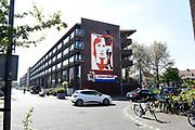 De weduwe van Johan Cruijff, Danny Cruijff, heeft dinsdagavond samen met burgemeester Eberhard van der Laan in Amsterdam-Oost een reusachtige muurschildering ter nagedachtenis aan de voetballegende onthuld.<br /> <br /> Het kunstwerk is geschilderd op een muur van een huizenblok op de hoek van de Wembleylaan en de Anfieldroad. Dat ligt bij het voormalige terrein van het oude Ajax-stadion De Meer in de Watergraafsmeer en tegenover Betondorp waar Cruijff opgroeide.