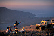 Hummer SUV and tourists picnic at sunset on top of hills above Two Harbors, Catalina Island, California Coast