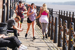 © Licensed to London News Pictures. 21/04/2020. Liverpool, UK. People are seen running alongside the Royal Albert Dock  on a warm day in Liverpool. The British Government imposed nationwide lockdown to minimise the spread of coronavirus disease COVID-19.  Photo credit: Ioannis Alexopoulos /LNP