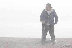© Licensed to London News Pictures. 14/09/2015. Brighton, UK. A man sitting on the beach during a rain storm. Brighton and the South Coast is being battered by strong winds and powerful waves. Today September 14th 2015. Photo credit : Hugo Michiels/LNP