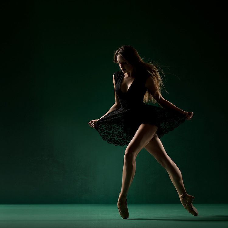 Contemporary female dancer, Cassandra Lewis, in a black dress, taken in the photo studio on a green background. Photograph taken in New York City by photographer Rachel Neville.