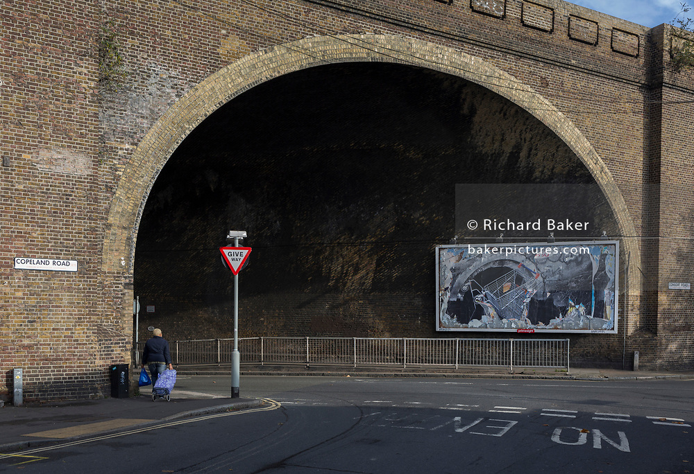 A billboard featuring a a supermarket trolley falling into a drain located beneath the arch of a Victorian-era railway bridge over the road in Peckham, on 16th November 2017, in south London, England.