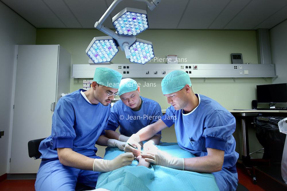 Nederland, Amsterdam , 20 juli 2011..De 2 Surinaamse studenten Donavon Heidanus (l) en Sue Fa Liu tijdens hun coschap in VUmc krijgen uitleg omtrent een handcorrectie op de poli plastische chirurgie..Foto:Jean-Pierre Jans
