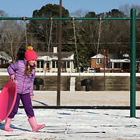 Vivian Galjour, 7, of Tupelo, heads back to the top of the hill, with her sled in hand to enjoy another ride down on Wednesday morning behind Church Street School in Tupelo.