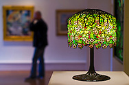 Roslyn, New York, U.S. - April 12, 2014 - During International Slow Art Day, visitors view a Tiffany Studios stained glass table lamp, Chanson de printemps after Bouguereau, and other artwork in the Garden Party exhibit at the Nassau County Museum of Art on Long Island. During this annual worldwide event, those participating (not known if person shown is participant) went to local museums and viewed a small number of works of art, each for at least 10 minutes, and then discussed them afterward.