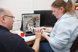Woman with a mild learning disability working as a trainee computer technician,  helped into employment by the Ready 4 Work team, Nottinghamshire County Council, with trainer