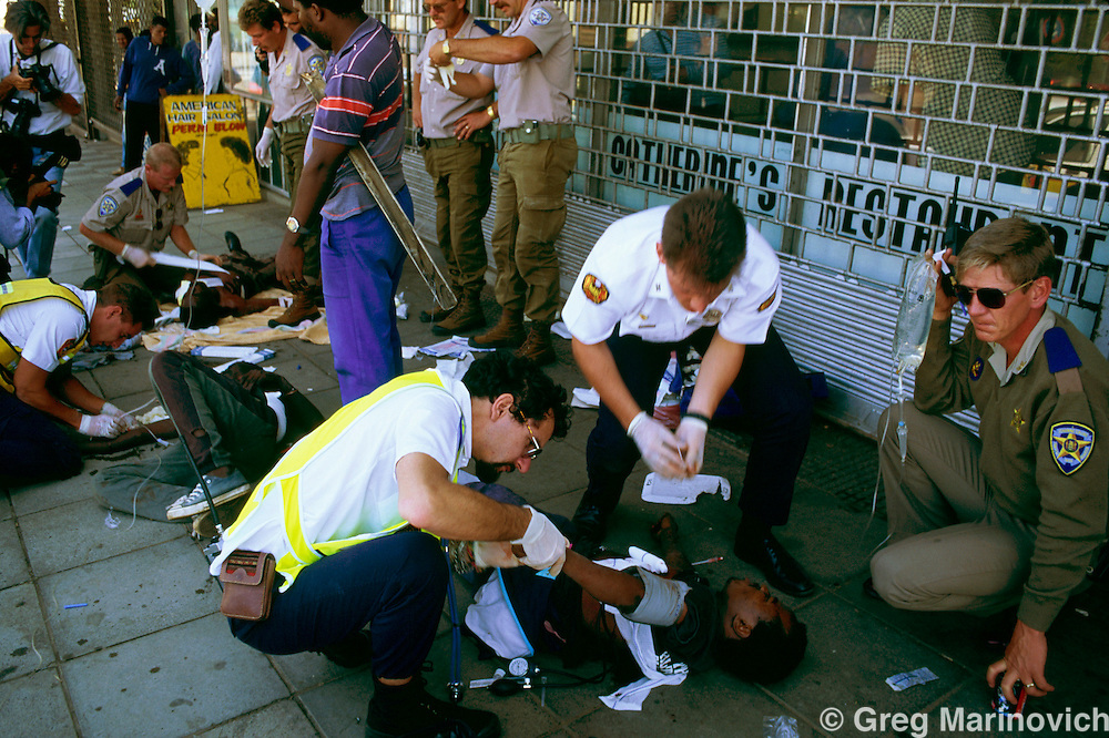 Johannesburg, South Africa, 1994.Medics treat the wounded after  African National Congress guards opened fire on Inkatha Freedom Party marchers when they approached the ANC headquarters of Shellhouse, Johannesburg 1994. Many IFP supporters killed and wounded. Others were shot from the rooftops by persons unknown at the nearby Library Gardens. Johannesburg, South Africa