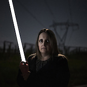 "Mirella holds a neon tube which, because of the Tesla effect, ignites spontaneously under the wires of a power line. ""I had a dream: to start a new life with a new family. A new home in the land inherited from my parents. A project in which I had put all my expectations, which were destroyed when I learned from the city hall that I was no longer allowed to lay one single brick on my land""."