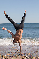 shirtless man doing a one handed handstand on the beach