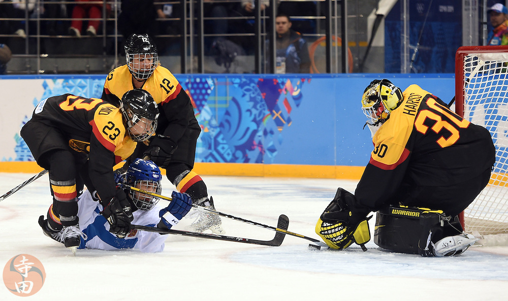 Feb 16, 2014; Sochi, RUSSIA; Finland forward Emma Nuutinen (96) tries to get to the puck between Germany goalkeeper Jennifer Harss (30) and defenseman Tanja Eisenschmid (23) in the women's ice hockey classifications round during the Sochi 2014 Olympic Winter Games at Shayba Arena.