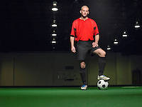 Soccer player standing on ball portrait