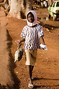 A girl carrying a chicken. At the confluence of the Niger and the Bani rivers, between Timbuktu and Segou, Mopti is the second largest city in Mali, and the hub for commerce and tourism in this west-african landlocked country.