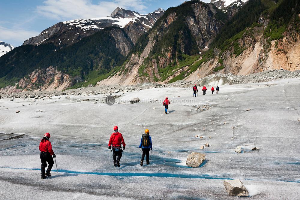 A group of tourists walk on a glacier near Juneau, Alaska.