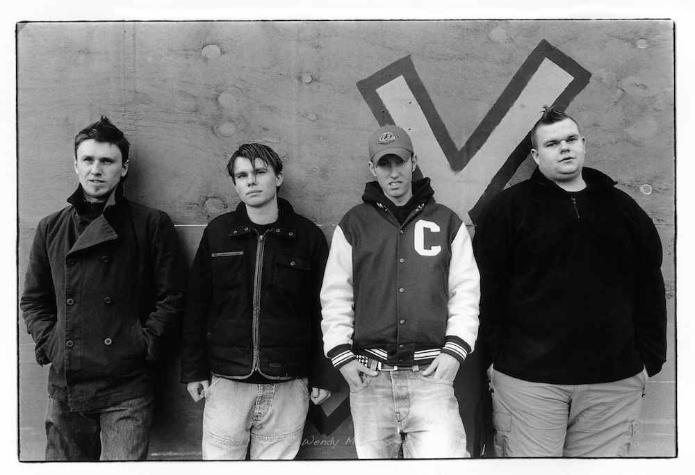 Belgian punk band Janez Detd in front of a grafitti wall. Turnhout, Belgium, 2003