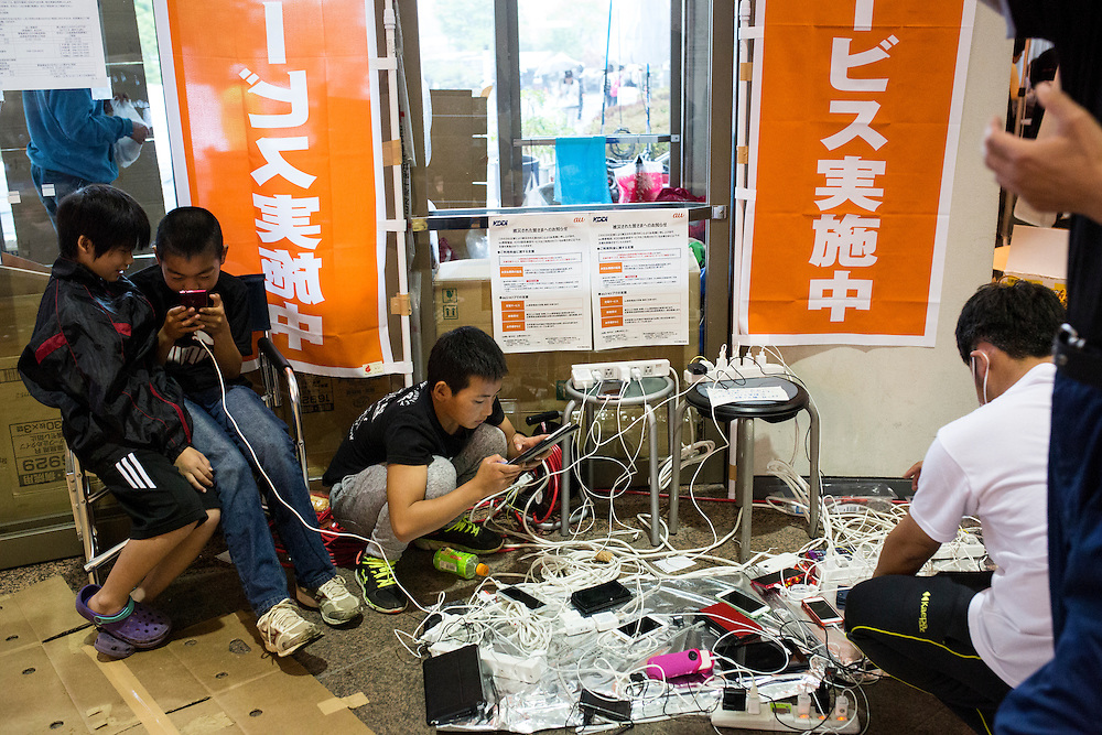 KUMAMOTO, JAPAN - APRIL 21:  Earthquake survivor charge their mobile phones in the morning of April 21, 2016 in Mashiki Gymnasium parking area, Kumamoto, Japan. To date 45 people are confirmed dead and around 11,000 people have evacuated after an 6.5 earthquake on Thursday night and a stronger 7.3 quake on Saturday morning struck the Kyushu Island in western Japan.<br /> <br /> Photo: Richard Atrero de Guzman