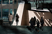 Group of woman walking through the Broadgate corporate offices development in the City of London. Either as a group of four, or as individuals, the ladies walk under tall steel architecture with the backdrop of the Broadgate development within the ancient boundary of the capital's Square Mile, it's financial district founded by the Romans in AD43.