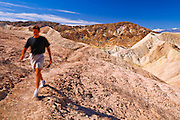 Hiker and colorful mineral deposits below Zabriskie Point, Death Valley National Park. California