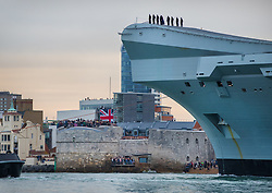 © Licensed to London News Pictures. 16/08/2017. Portsmouth, UK. The Royal Navy's new aircraft carrier HMS Queen Elizabeth passes crowds on the Round Tower as she enters her home port of Portsmouth for the first time. The new ship at 65,000 tonnes is the biggest warship ever built in the UK. Photo credit: Peter Macdiarmid/LNP