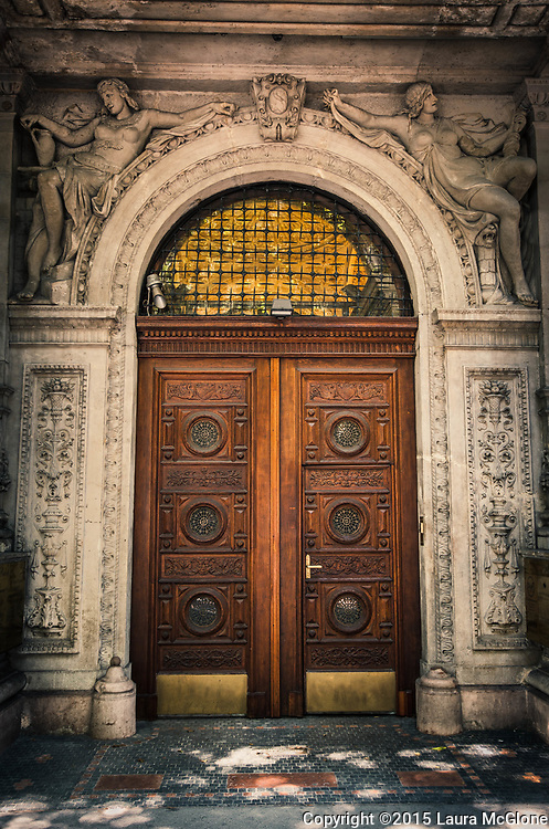 Brown wooden carved door with detailed amazing stone surround, Budapest Hungary