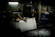 A Burmese migrant working illegally in Saphan Pla fish market in Bangkok,He sell ice blocks to shrimp packers.   Un migrant birman travaillant illégalement au marché aux poissons de Saphan Pla à Bangkok, vend des blocs de glace à des pêcheurs de crevettes.