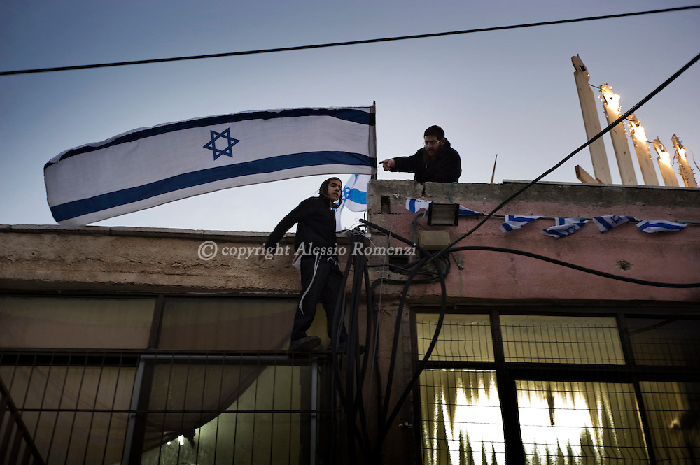 .JERUSALEM: Two Religious Jewish install the israeli flag on the roof of the disputed house on December 17, 2009  in Sheikh Jarrah, a neighbourhood of Arab east Jerusalem where several Palestinian families have been evicted to make way for Israeli settlers who claim legal ownership. The international community considers Jewish neighbourhoods in east Jerusalem to be Israeli settlements and the issue of settlements in the Palestinian territories is one of the main obstacles in the hobbled Middle East peace process. Israel captured east Jerusalem from Jordan in the 1967 Six Day War and later annexed it as its 'eternal and indivisible' capital in a move not recognised by the international community...© ALESSIO ROMENZI