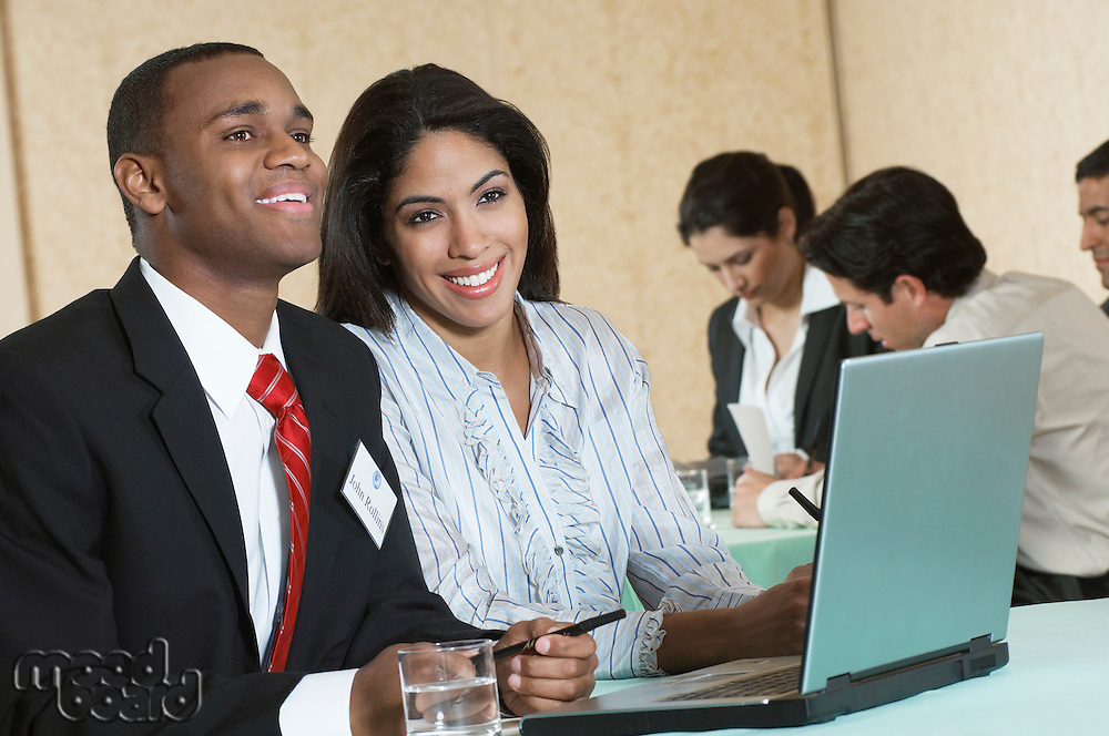 Business man and woman using laptop at conference meeting