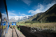 Two railroad trains pass each other in the Sacred Valley of Peru.