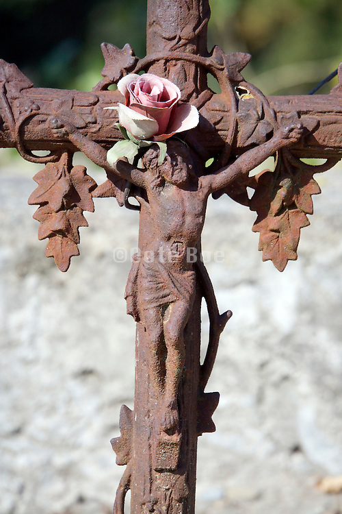 artificial flower placed on a rusty cross that is the headstone at a small graveyard