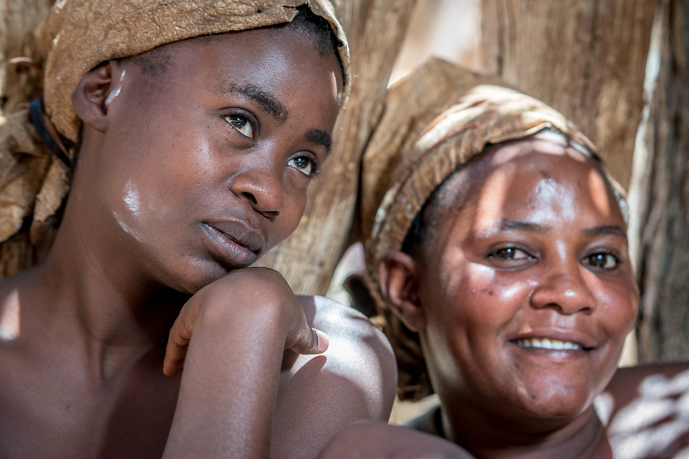 Damaran women sit and pose together in the shade at the Damara Living Museum, located north of Twyfelfontein in Namibia, Africa.