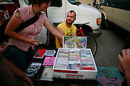 Christopher Johnston, AKA Chis Clavin, who operates Plan-it-X records, which he says is not a business but a way to distribute music he likes for friends, sells compact discs for five bucks at a table in a parking lot during the Plan-it-X festival.
