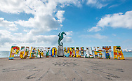 """Puerto Vallarta sign on the Malecon with """"Caballero del Mar"""" the sculpture of a seahorse ridden by a boy by artist Rafael Zamarripa, 1976. Blue sky and white puffy clouds above and no people in view."""