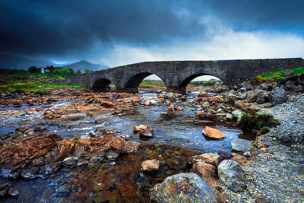 Old stone bridge crossing a shallow river in Scotland under a stormy sky