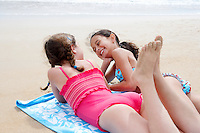 Pre-teen girls lying side by side on stomach on beach towel on sandy beach talking
