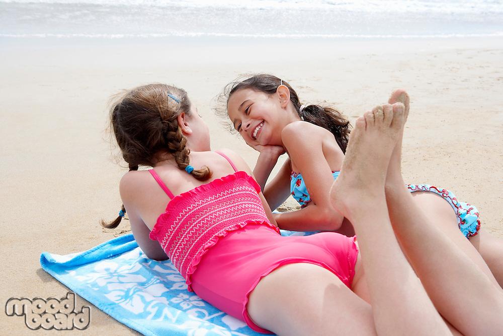 Pre-teen girls lying side by side on stomach on beach towel on sandy beach talking