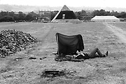 Man relaxing next to wind shelter in front of the Pyramid stage Glastonbury, 1989.