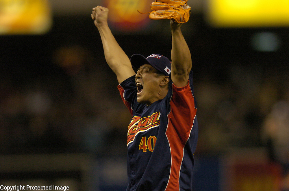 Team Japan's Akinori Otsuka raises his arms after beating Team Cuba 10-6 in Final action of the World Baseball Classic at PETCO Park, San Diego, CA.