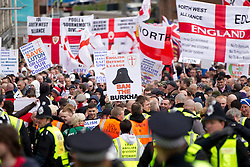 "© Licensed to London News Pictures. 05/05/2012. Luton, UK. A man holds a placard reading ""Ban the burkha"" at an EDL march in Luton. The EDL hold a march and demonstration in Luton town centre. About 1500 EDL supporters attended and about 1200 police. A counter protest was also held. Photo credit : Joel Goodman/LNP"