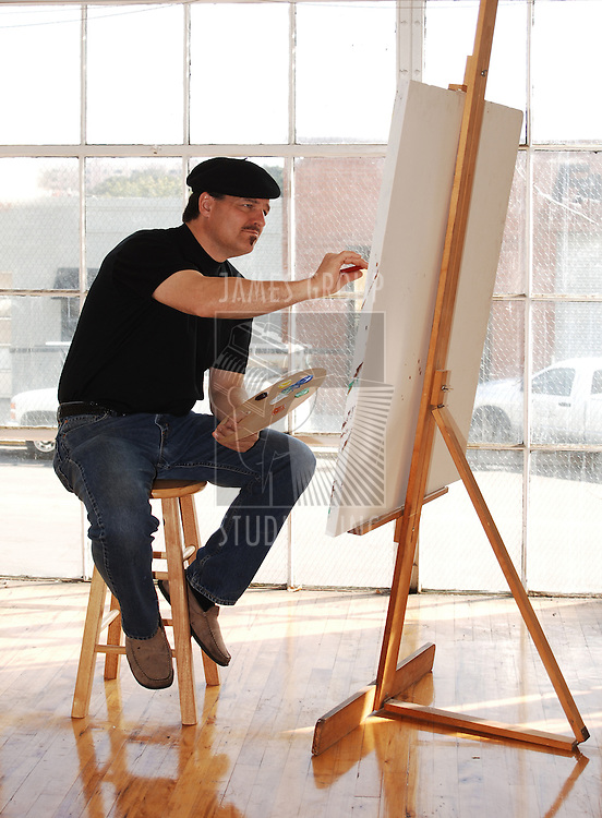 Artist painting on canvas in studio wearing beret and holding paint palette