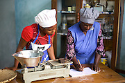 Joyce Marwa (right) doing some record keeping. <br /> <br /> Joyce set up and now runs a bakery that bakes bread and cakes. She also processes nutritious flour (a mix of 5 grains)<br /> <br /> She attended MKUBWA enterprise training run by the Tanzania Gatsby Trust in partnership with The Cherie Blair Foundation for Women.