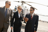 Businesspeople communicating with helicopter in background